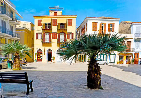 The tiny park in Plapouta street, in front of St George church, with benches, palm trees and a view on the old residential houses, Nafplio, Greece