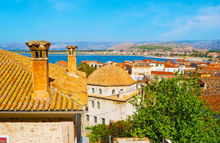 Enjoy the top view of Nafplio old town with red tile roofs, chimneys, large dome of Trianon old mosque and Argolic Gulf coast in background, Greece Banco de Imagens