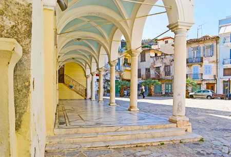 The exterior of St George church with preserved colonnade and a view on Plapouta street with old housing, Nafplio, Greece Banco de Imagens