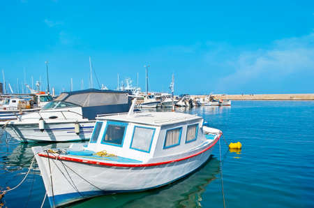 The line of fishing and tourist boats, moored in Venetian harbor of Chania, Crete, Greece Banco de Imagens