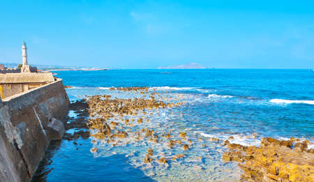 The rocky coast of Chania Bay with a view on medieval stone breakwater and Venetian lighthouse, Crete, Greece Banco de Imagens