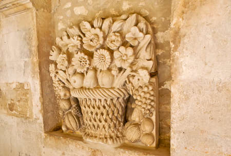 The beautiful wall sculpture of bouquet of flowers and fruits in basket, located in cloister of medieval Saint-Paul de Mausole Monastery, Saint-Remy-de-Provence, France