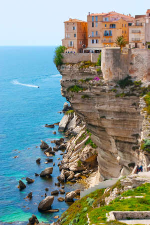 Enjoy the rocky landscape of Bonifacio with a view on the medieval houses of Ville Haute (upper town), towering the limestone cliff, Corsica, France Banco de Imagens