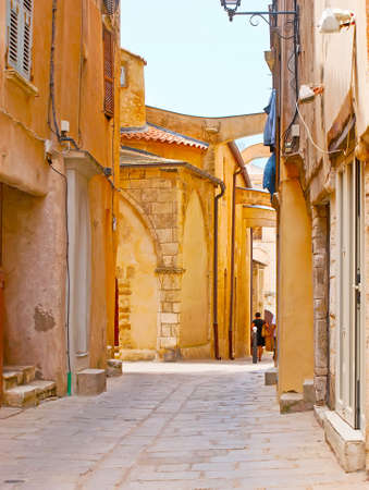 The narrow street of Ville Haute (upper town) with a view on the wall of Sainte-Marie-Majeure Church with flying buttresses, Bonifacio, Corsica, France