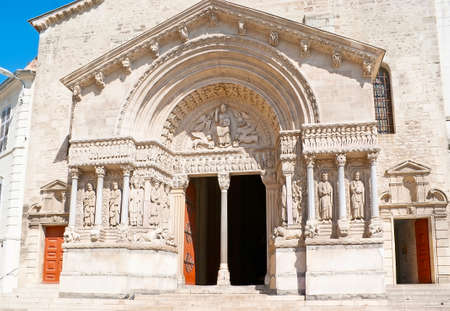 The ornate Romanesque gate of the medieval St Trophime Cathedral with carved patterns, wall sculptures and columns, Arles, France Banco de Imagens