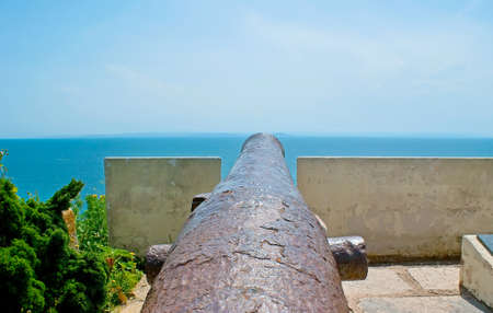 The rusty cannon on the edge of the cliff in Bonifacio is a part of War Memorial, Corsica, France