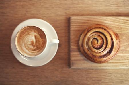 cappucino: Cappucino and bun with cinnamon on wooden table Stock Photo