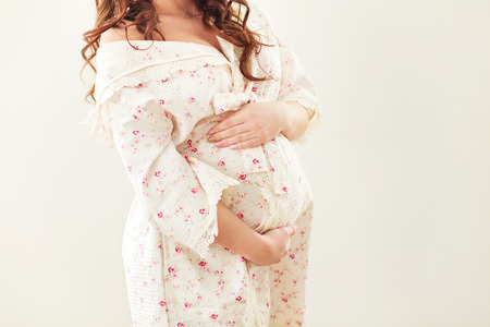 expectant arms: Pregnant woman in soft robe touching her belly with hands Stock Photo