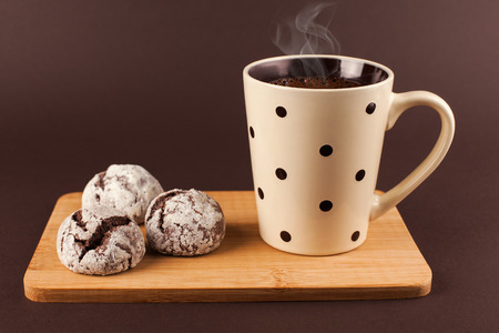 Cup of coffee with foam, with cookies, lying on the wooden stand, on brown background