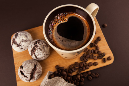 Cup of coffee with foam, heart shaped, with cookies and coffee beans, lying on the wooden stand, on brown background