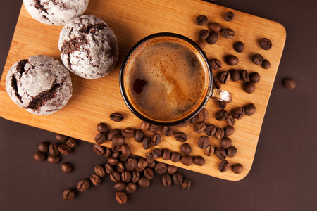 coffee cake: Cup of coffee with foam, with cookies and coffee beans, lying on the wooden stand, on brown background