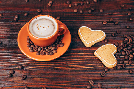 energizing: Ceramic orange cup of coffee with foam, with heart shaped cookies and coffee beans, lying on wooden table