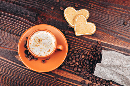 Ceramic orange cup of coffee with foam, with heart shaped cookies and coffee beans, standing on wooden table photo