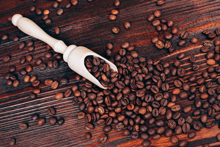 wooden scoop: Wooden scoop with coffee beans lying on wooden table