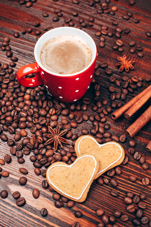 anice: Cup of coffee with foam, cinnamon sticks, star anice, coffee beans and wooden board with heart shaped cookies, staying on the wooden table