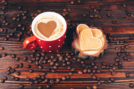 energizing: Cup of coffee with foam, heart shaped, with heart shaped cookies and coffee beans, lying on the wooden stand, on wooden table Stock Photo