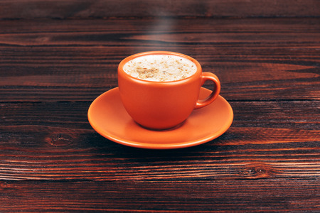 energizing: Ceramic orange cup of coffee with foam, standing on wooden table on wooden background
