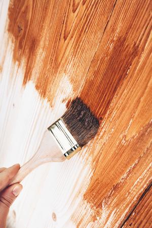 Varnishing a wooden shelf using paintbrush