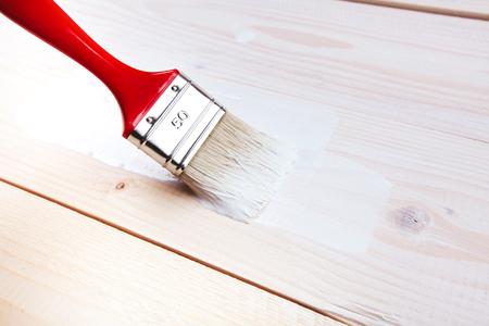 Varnishing and painting a wooden shelf using paintbrush Standard-Bild