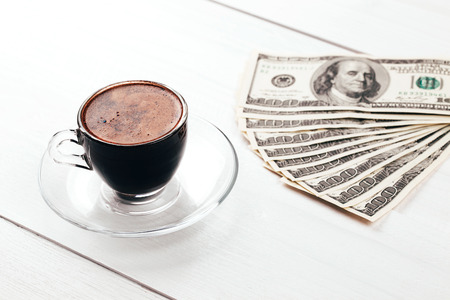 Cup of aromatic espresso in glass with fan of dollars, hundred banknotes, lying on white wooden table photo