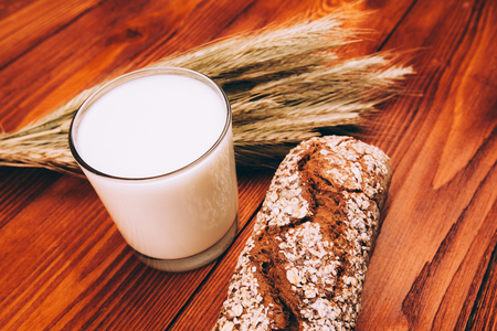 Glass of milk with breaf lying on wooden table photo
