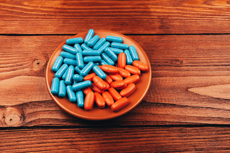 Colored pills lying on wooden table photo
