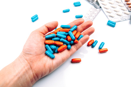 Colored pills in the hand, blue and orange, capsule Standard-Bild