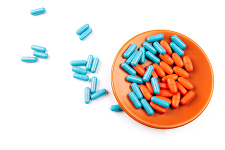 Colored pills on the plate isolated on white photo