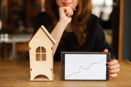 Young smiling woman holding model of house and digital tablet with diagram