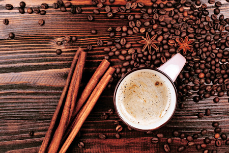 anice: Cup of coffee with foam, cinnamon sticks, star anice, coffee beans and place for text, staying on the wooden table Stock Photo