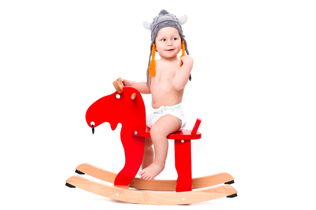 asterix: Funny cute baby sitting on the toy horse or elk in Asterix hat, smiling isolated on white Stock Photo