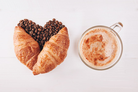 cappucino: Heart made with croissant and coffee beans lying on white wooden table with cup of coffee or cappucino Stock Photo