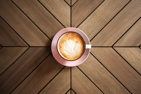 cappucino: Cup of cappucino on wooden table with graphic lines
