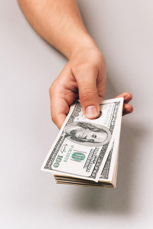 Hand holding and giving money in dollars Standard-Bild
