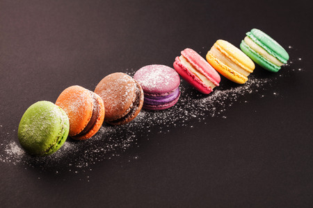 Row of french colorful macaroons with powdered sugar, lying on black background Stock Photo