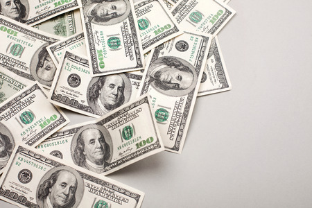 pile of money: money american hundred dollar bills - horizontal on grey background Stock Photo