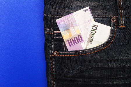 swiss franc note: comparison of Swiss francs and euros with place for text lying in pocket of jeans on blue background