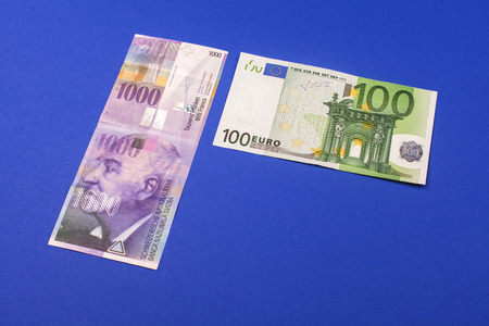 swiss franc note: comparison of Swiss francs and euros with place for text lying on blue background