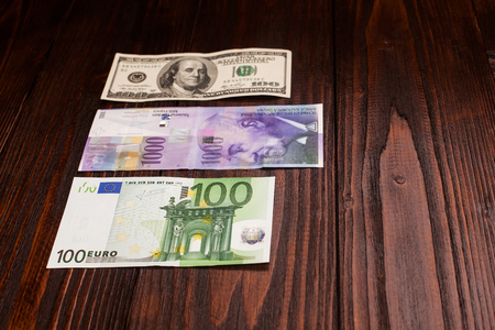 swiss franc note: comparison of Swiss francs dollars and euros on wooden table