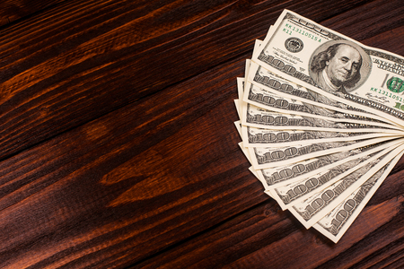 one hundred dollars: Fan of one hundred dollars banknotes lying on wooden table