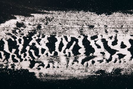heterogeneous: Flour are scattered in a striped pattern on black background, zebra background