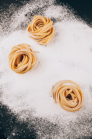 top view of pasta on scattered flour on a  black background with a place for text Фото со стока - 39238317