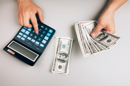 calculator: savings, finances, economy and concept - close up of man with calculator counting money Stock Photo