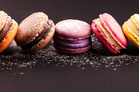 Row of french colorful macaroons with powdered sugar, lying on black background Фото со стока