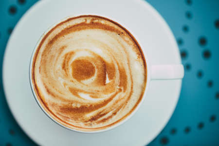 crema: White cup of coffee with crema on a round blue table with a  pattern