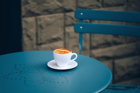crema: White cup of coffee with crema on a round blue table with a pattern  in street cafe