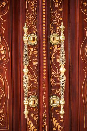 fretwork: Golden vintage door handles on a wooden door with a carved pattern Stock Photo