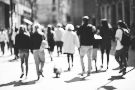 Blurred crowd of walking people in the city with buildings in the background, black and white Stock Photo