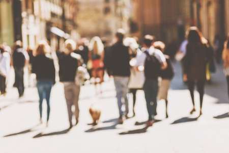 Blurred crowd of walking people in the city with buildings in the background Stock Photo