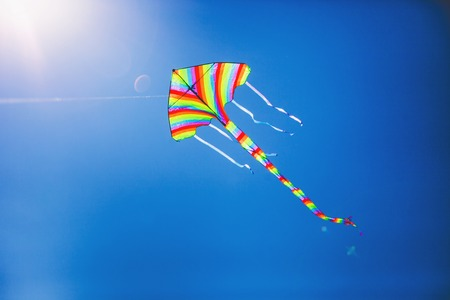 Striped kite flying against the blue sky on a sunny day photo
